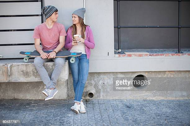 Young man with skateboard and teenage girl sitting outdoors