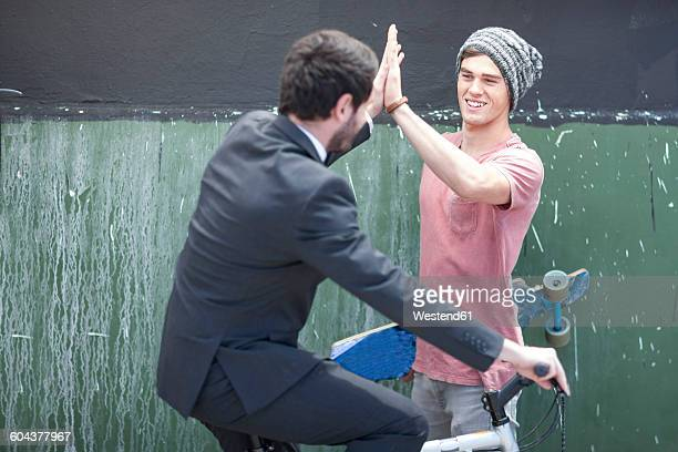 young man with skateboard high fiving with businessman on bicycle - gegensatz stock-fotos und bilder