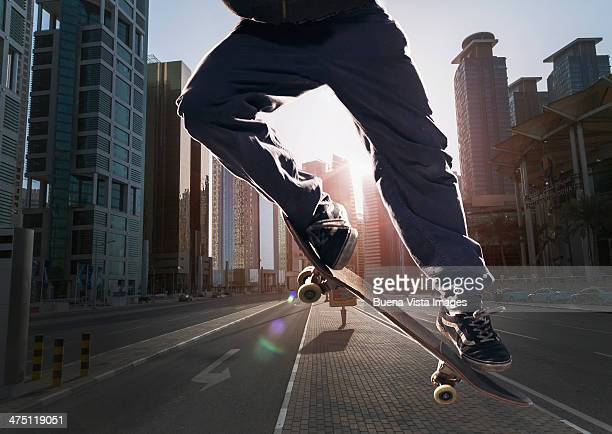 young man with skateboard in  a modern city