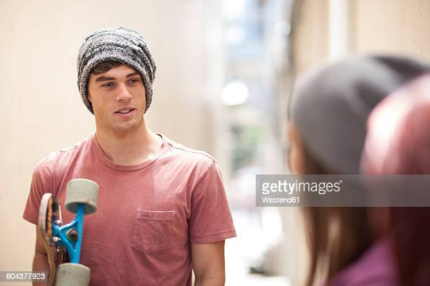 Young man with skateboard in a passageway talking to friends