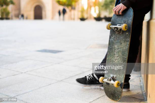 Young man with skateboard leaning against house front
