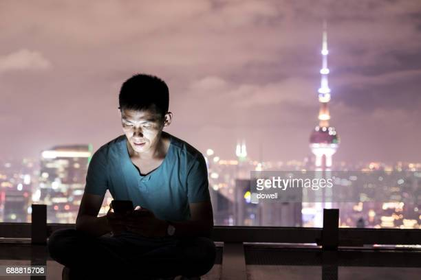 young man with smart phone in midtown of shanghai at night