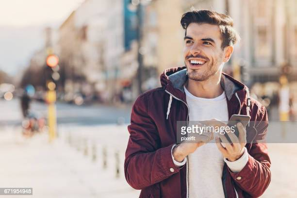 young man with smart phone in the city - young men stock pictures, royalty-free photos & images