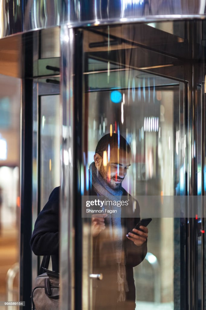 Young man with smart phone using revolving door : Stock Photo
