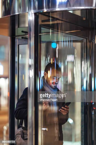 young man with smart phone using revolving door - revolve stock photos and pictures
