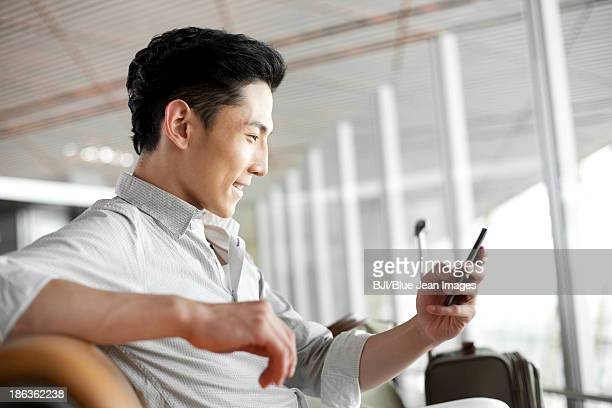 Young man with smart phone waiting in airport lounge