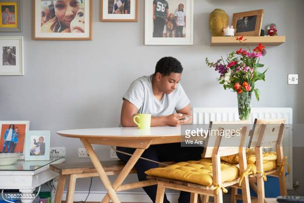 young man with smartphone at home - table stock pictures, royalty-free photos & images