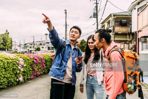 スマートフォンをポインティングし、バックパックで友人に話している若い男 - 観光 ストックフォトと画像