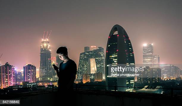 Young man with smartphone sitting on roof