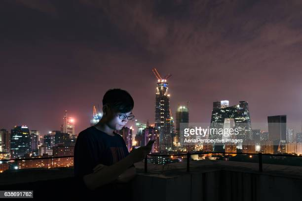Young Man with Smartphone Standing on Skyscraper Roof