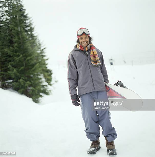 Young man with snowboard, portrait