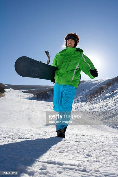 young man with snowboard walking - ski pants stock pictures, royalty-free photos & images