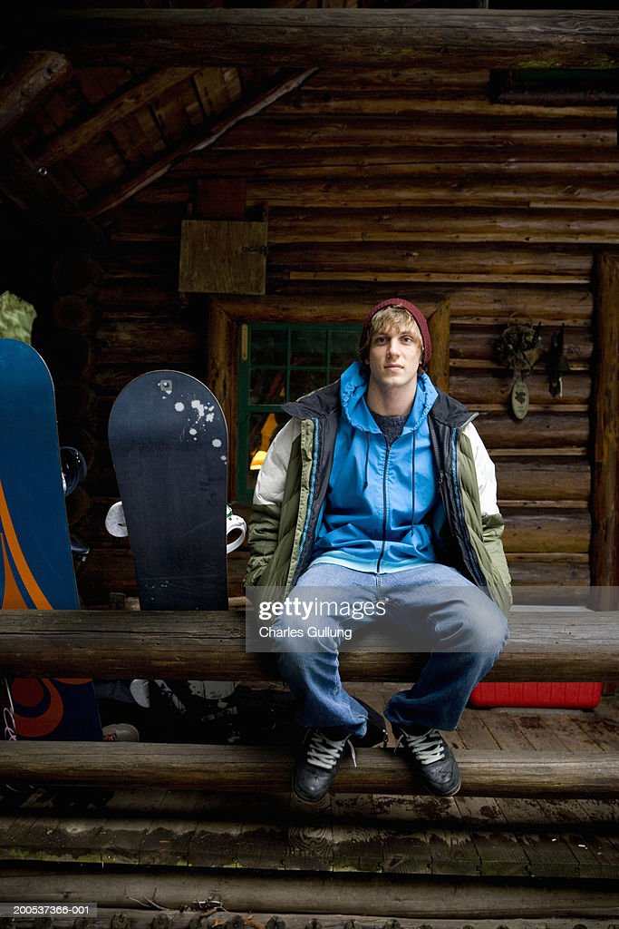Young man with snowboards sitting on railing outside log cabin : Stock-Foto