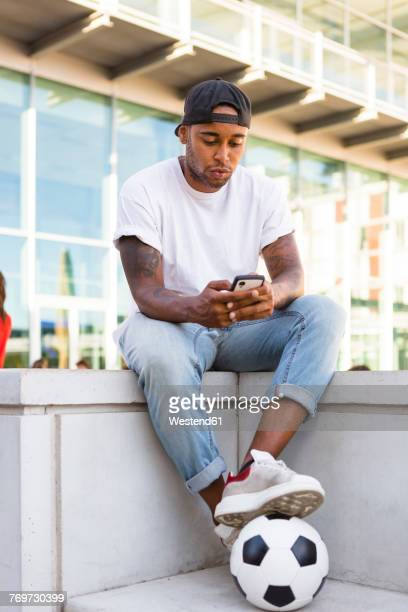 Young man with soccer ball isitting on a wall looking at cell phone