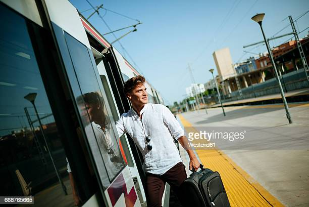 Young man with suitcase entering a train