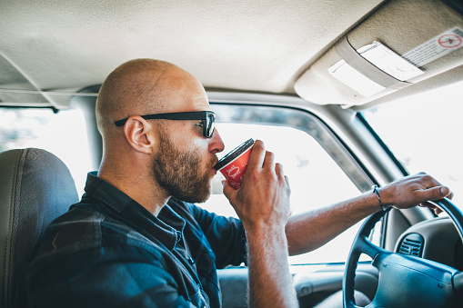 Young man with sunglasses and beard on a road trip with takeaway drink - gettyimageskorea
