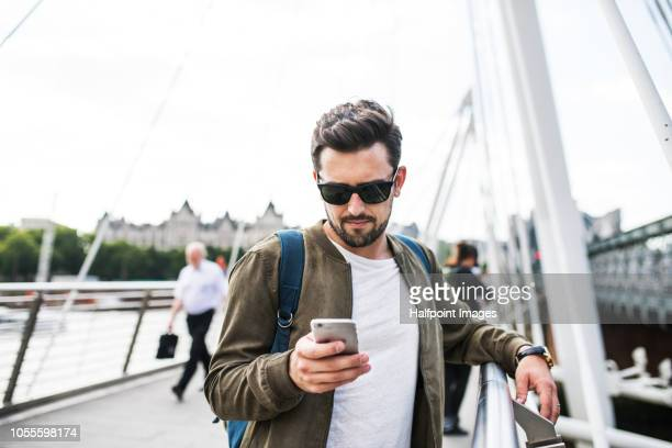 A young man with sunglasses and smartphone standing on the bridge, text messaging.