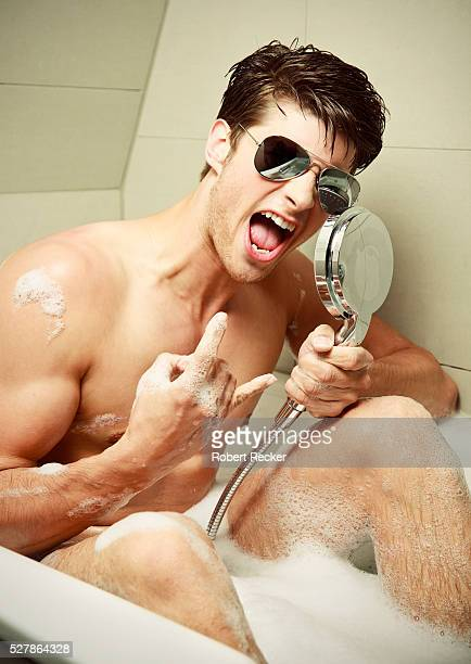 Young man with sunglasses singing in bathtub
