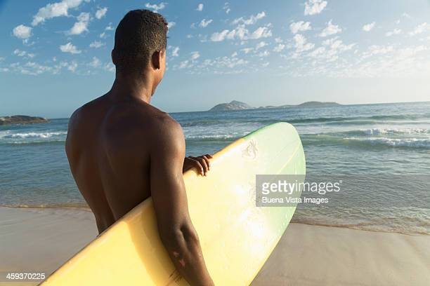 Young man with surfboard on the  beach