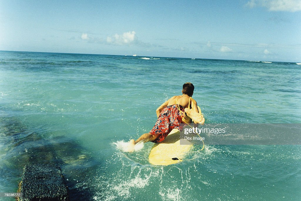 Young man with surfboard, rear view : Stock Photo