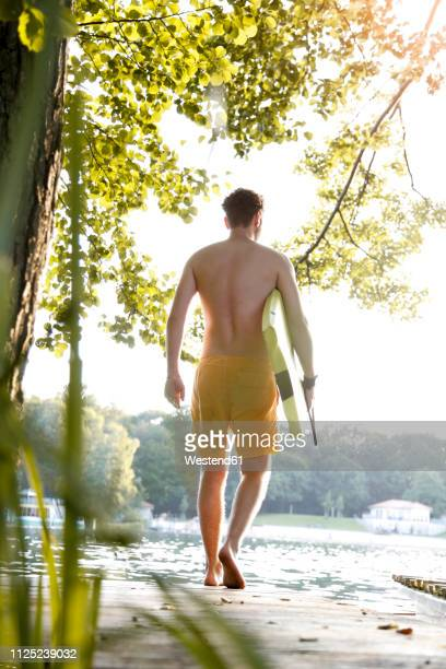 Young man with surfboard walking on a jetty at a lake