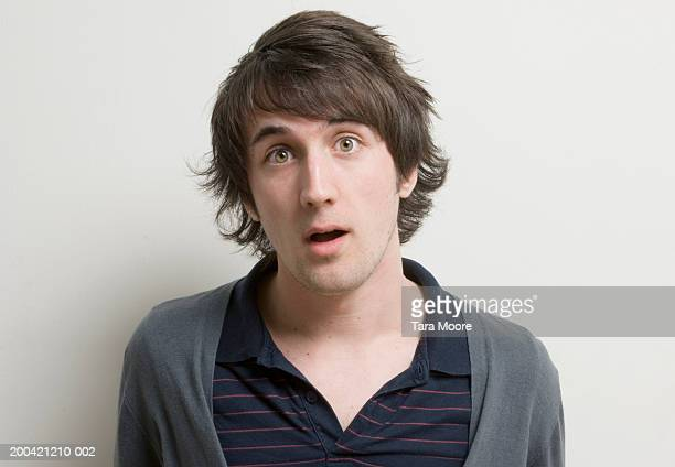 young man with surprised expression on face, portrait, close-up - medium length hair stock pictures, royalty-free photos & images