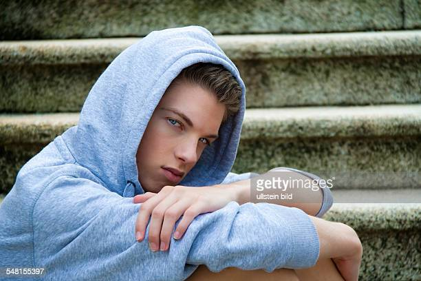young man with sweater sitting on stairs 2010