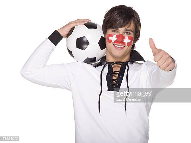 Young man with Swiss flag painted on face and carrying football on shoulders