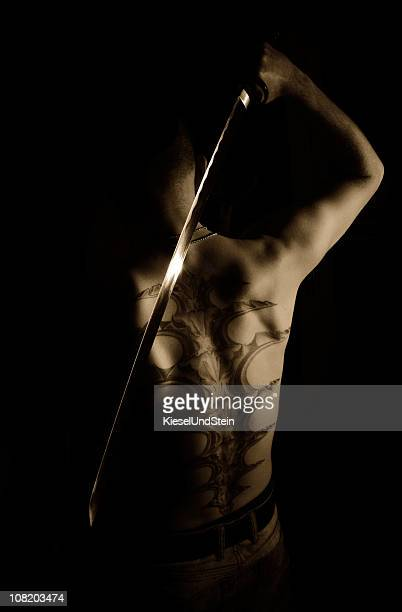 Young man with sword and tattoo