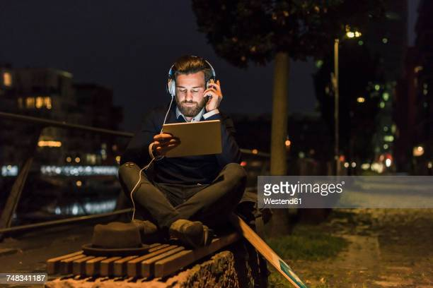 Young man with tablet and headphones in the city at night
