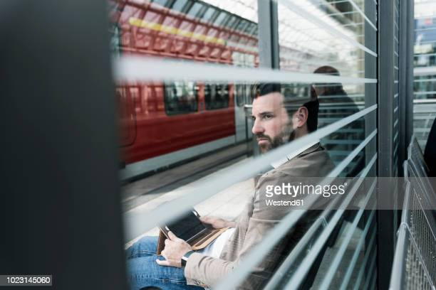 young man with tablet waiting at the station platform - passenger train stock pictures, royalty-free photos & images