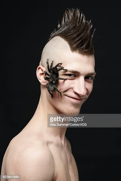 Young man with tarantula crawling on face