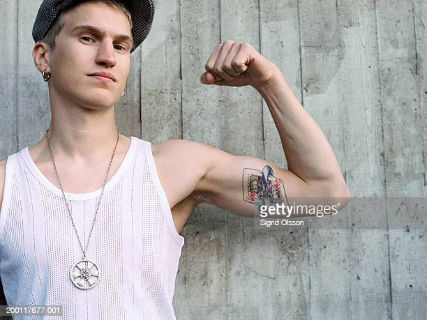 young man with tattoo, flexing arm, portrait - medallion stock photos and pictures