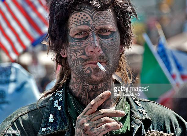 CONTENT] A young man with tattoos all over his face smoking a cigarette at a protest rally