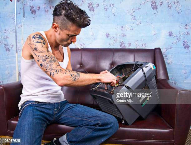 Young Man with Tattoos, Smoking and Repairing Television