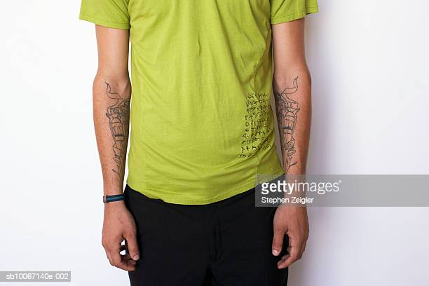 Young man with tattoos with forearms, mid section