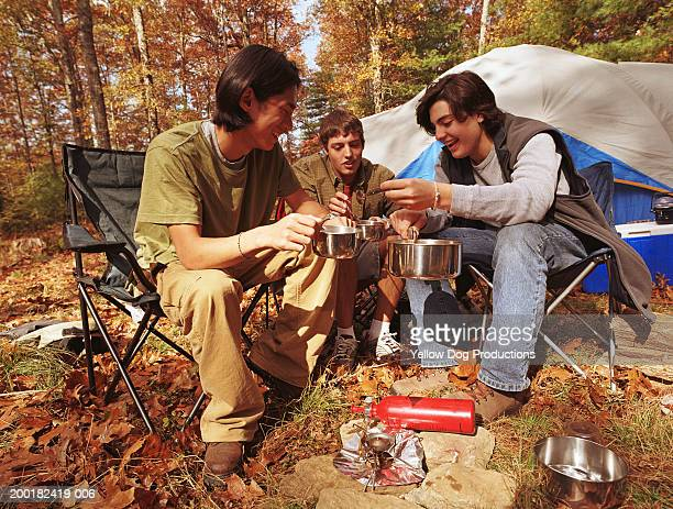 Young man with teenage boys (15-17) at campsite holding pots, smiling