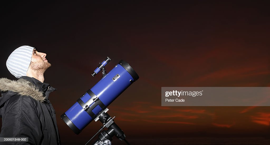 Young man with telescope looking at sky, dusk, side view : Foto de stock