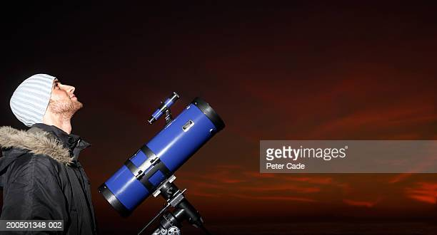 Young man with telescope looking at sky, dusk, side view