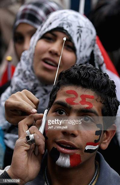 A young man with the date 25 painted on his face talks on a mobile phone in Tahir Square ahead of the first anniversary of the revolution on January...