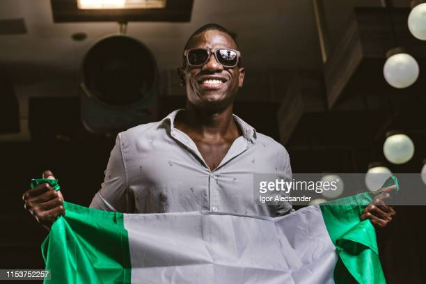 young man with the flag of the federal republic of nigeria - nigerian flag stock photos and pictures