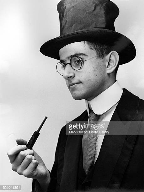 Young man with top hat smoking pipe mid 1920s