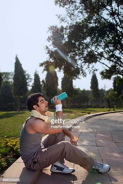 Young man with towel round shoulders drinking water after sport activities
