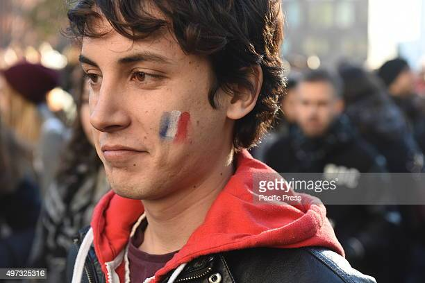 Young man with Tricolor face paint A day that began with a rally at Washington Square Park culminated in a candlelight vigil outside the French...