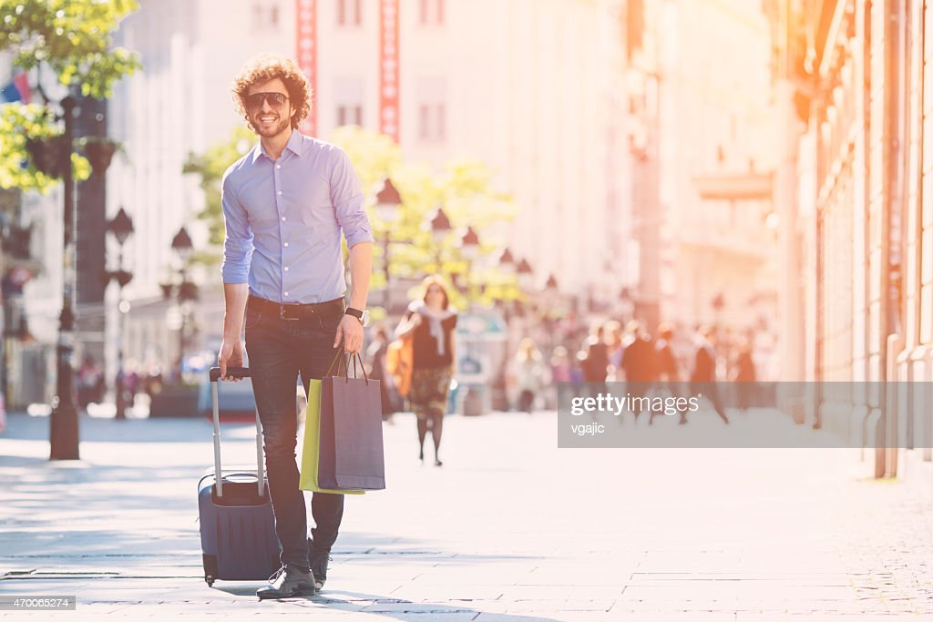 Young Man With Trolley Bag Walking in a city. : Stock Photo