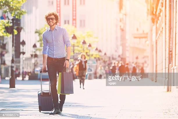 Young Man With Trolley Bag Walking in a city.