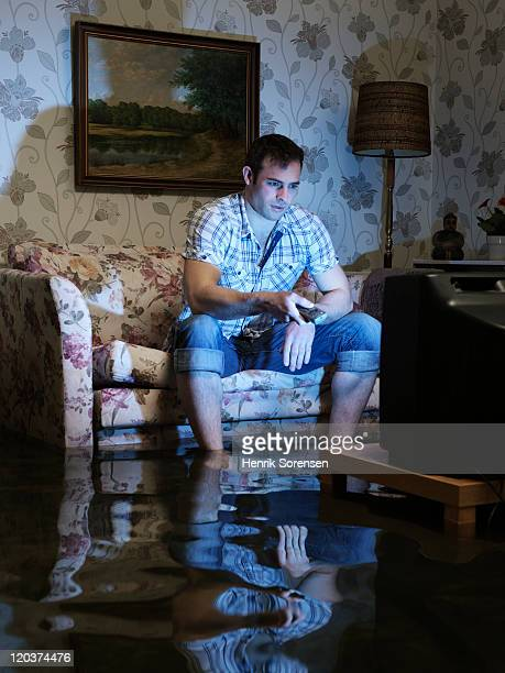 young man with TV in flooded room