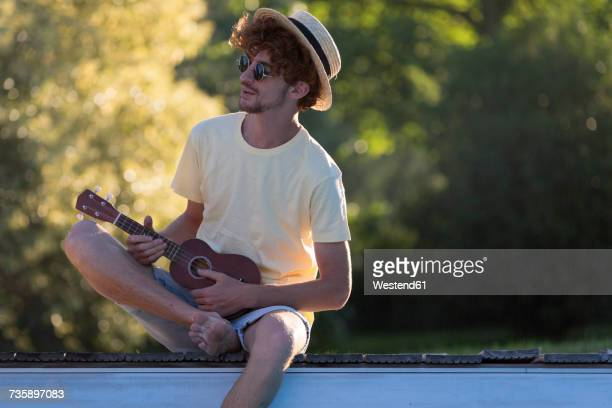 Young man with ukulele relaxing at pool edge