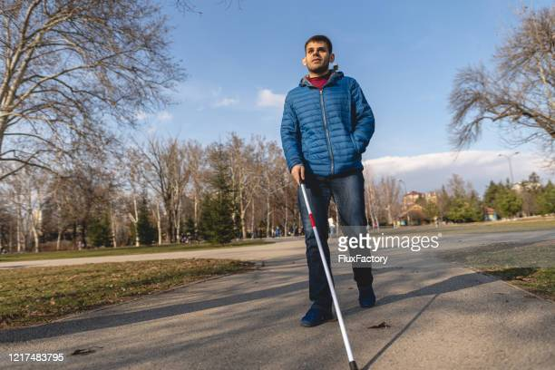 暖かい日に散歩を楽しむ視覚障害を持つ若者 - 白杖 ストックフォトと画像