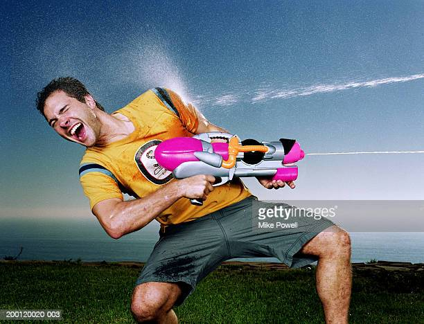 young man with water gun being hit with water blast  on arm - wet t shirt contest stock photos and pictures